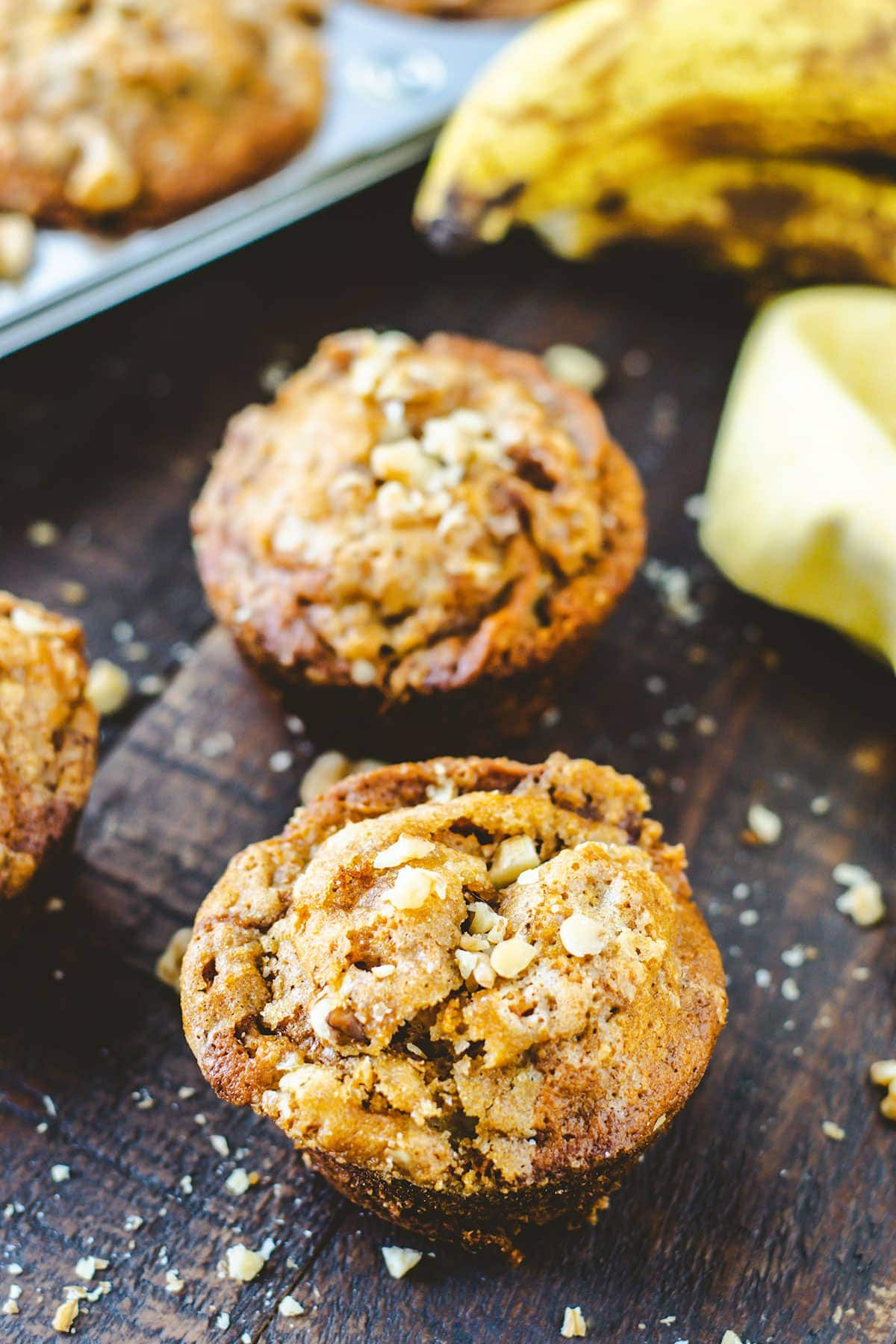 Banana Muffins topped with walnuts on a rustic tray.