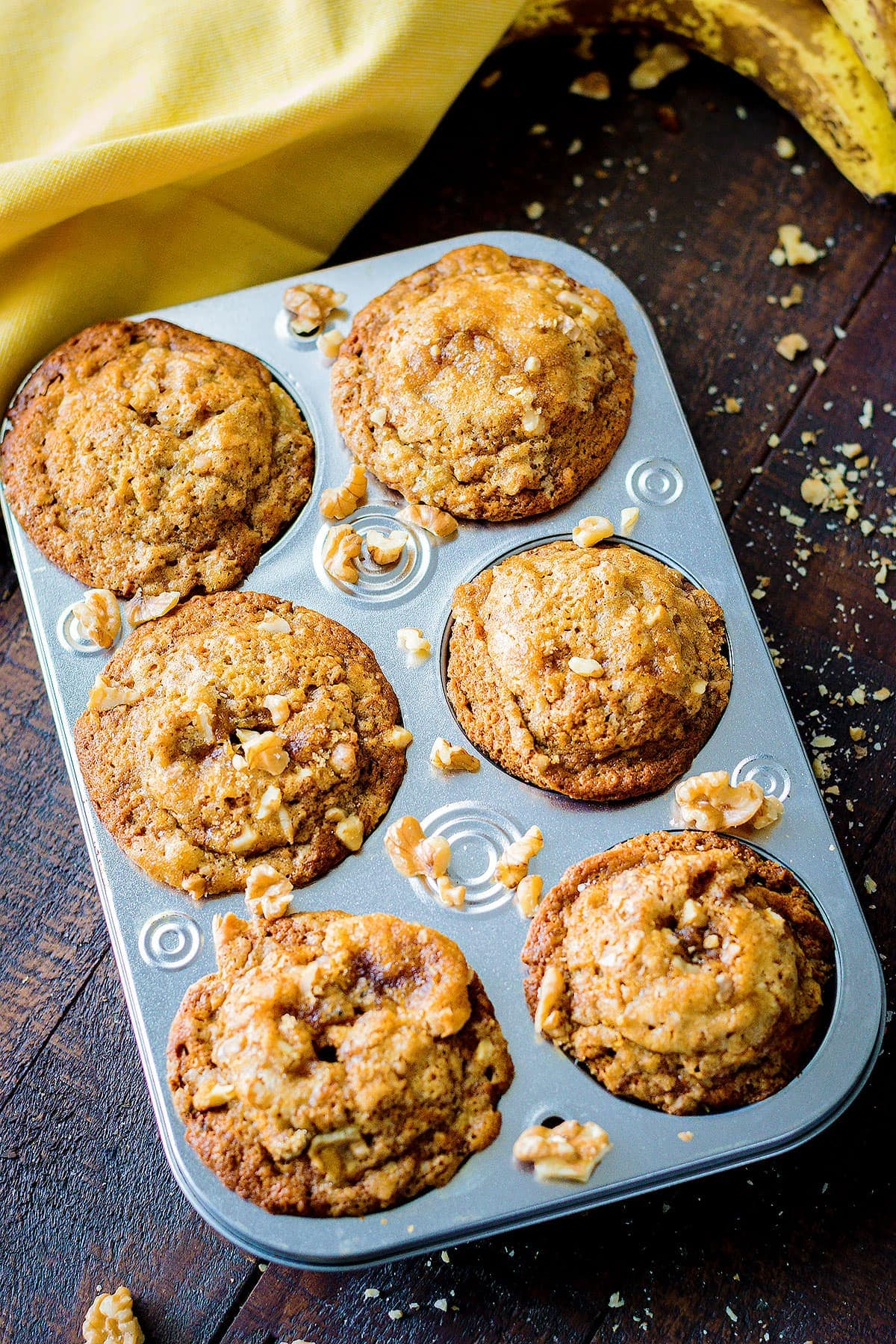 Muffins in a muffin tin surrounded by scatter walnuts on a wooden table with yellow napkin and bananas in the background.
