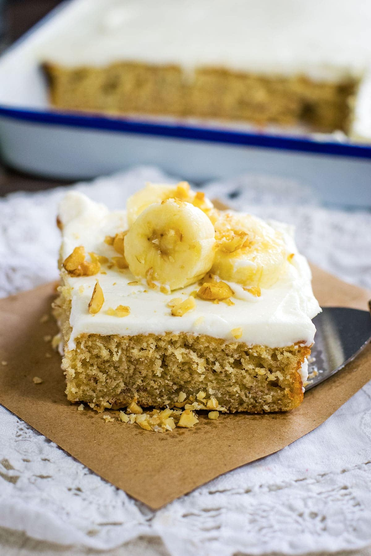 Slice of banana cake topped with bananas and walnuts