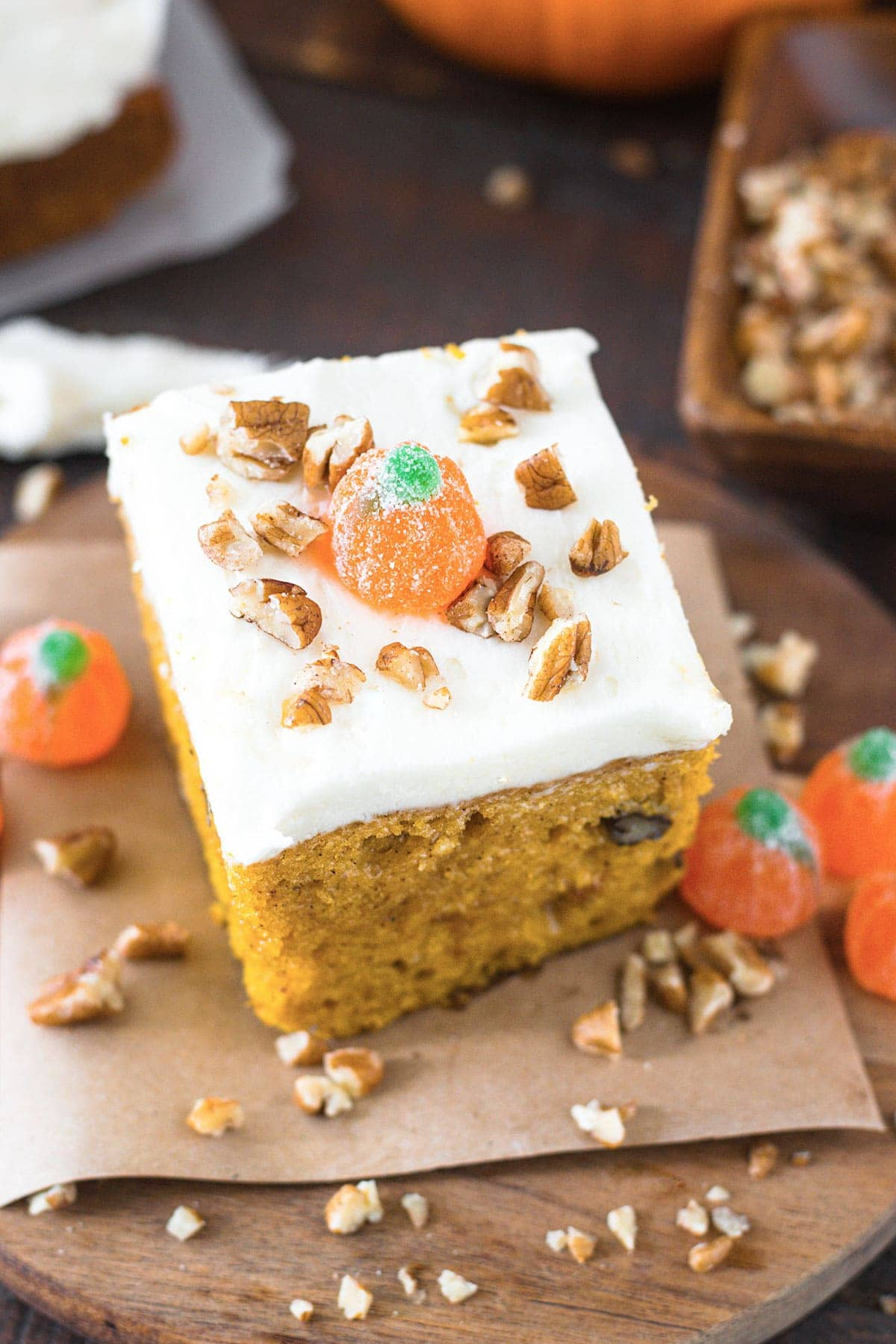 Slice of pumpkin cake topped with whimsical candy pumpkins and and pecan pieces.