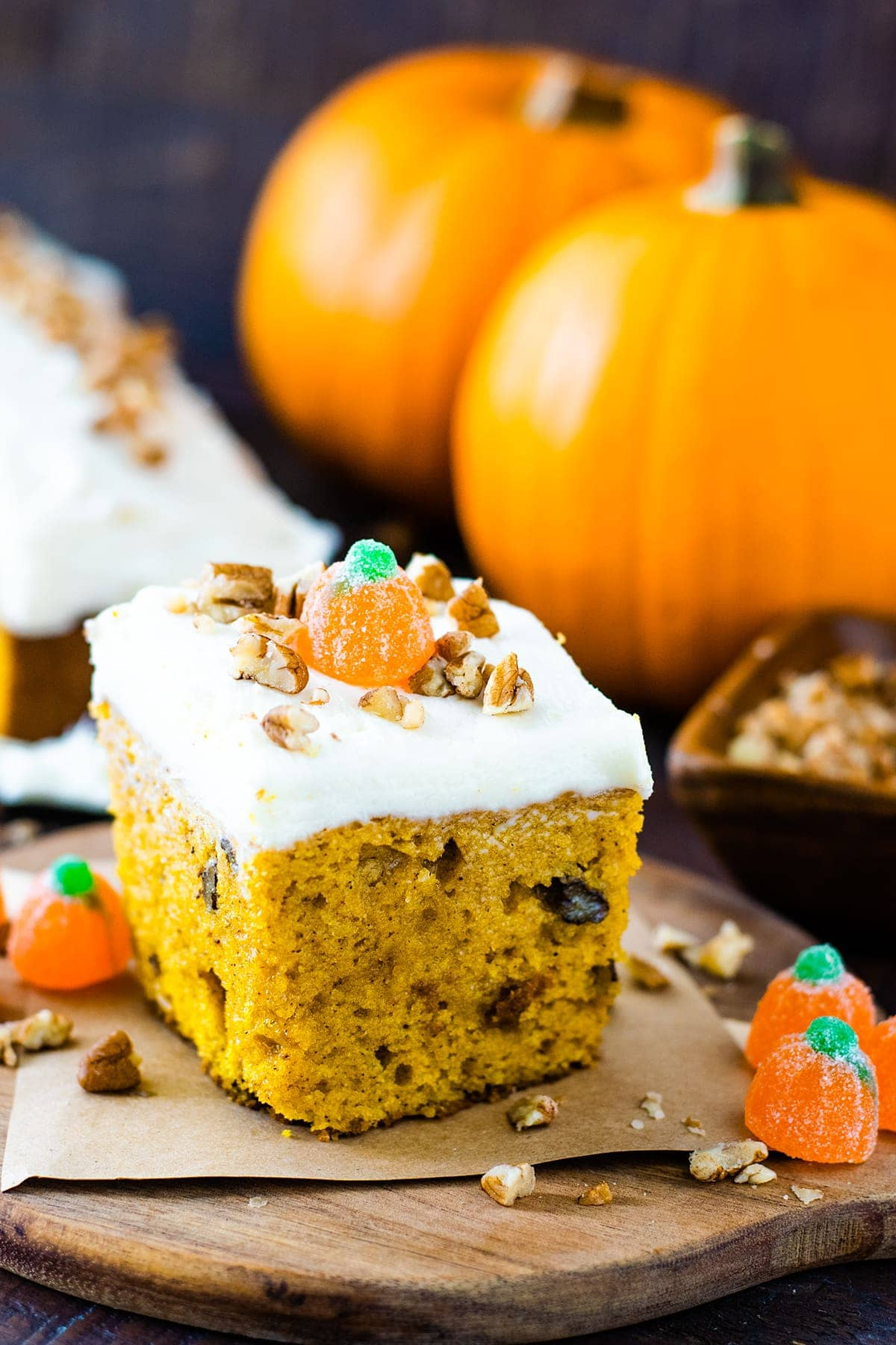 Slice of pumpkin spice cake with orange pie pumpkins displayed in the background.