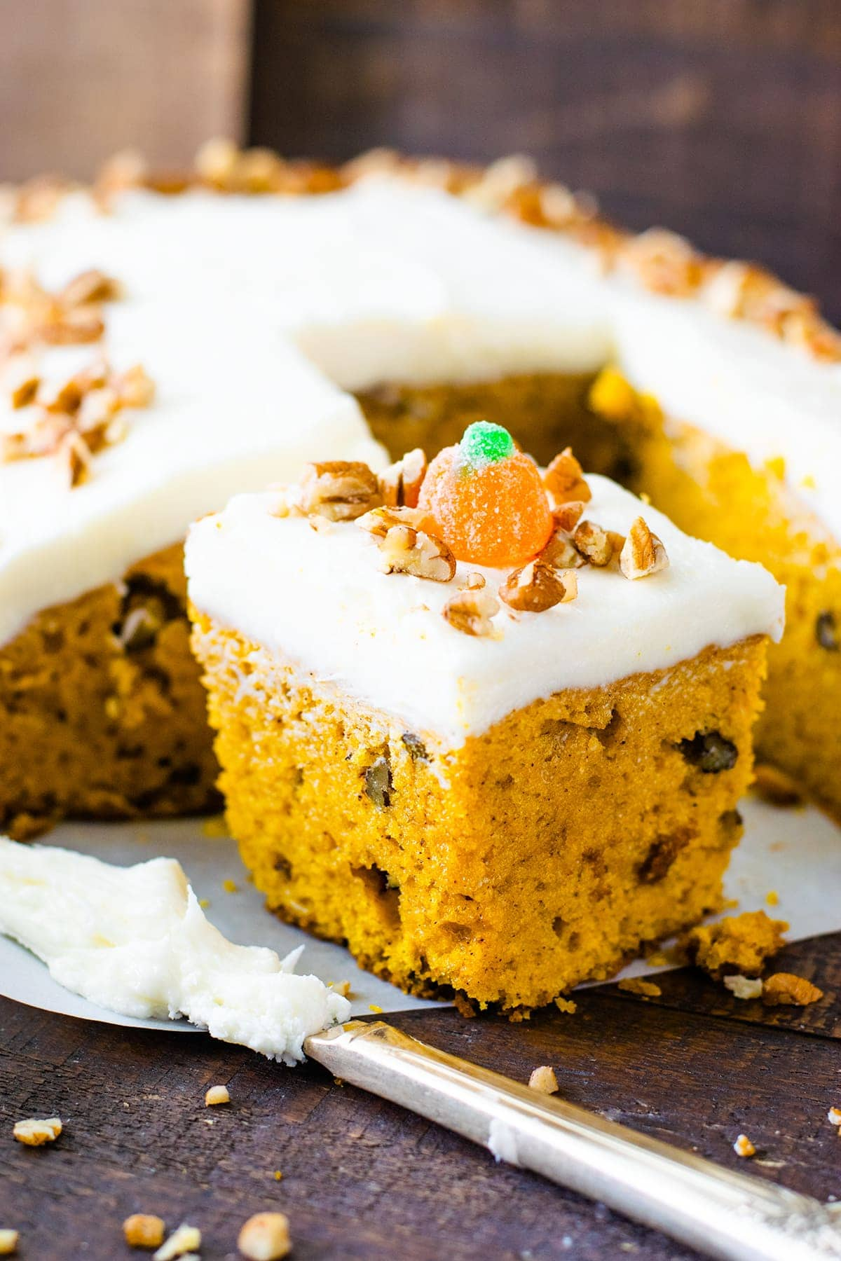 Slice of Pumpkin Spice Cake sprinkled with pecans and a candy pumpkin on a serving board.