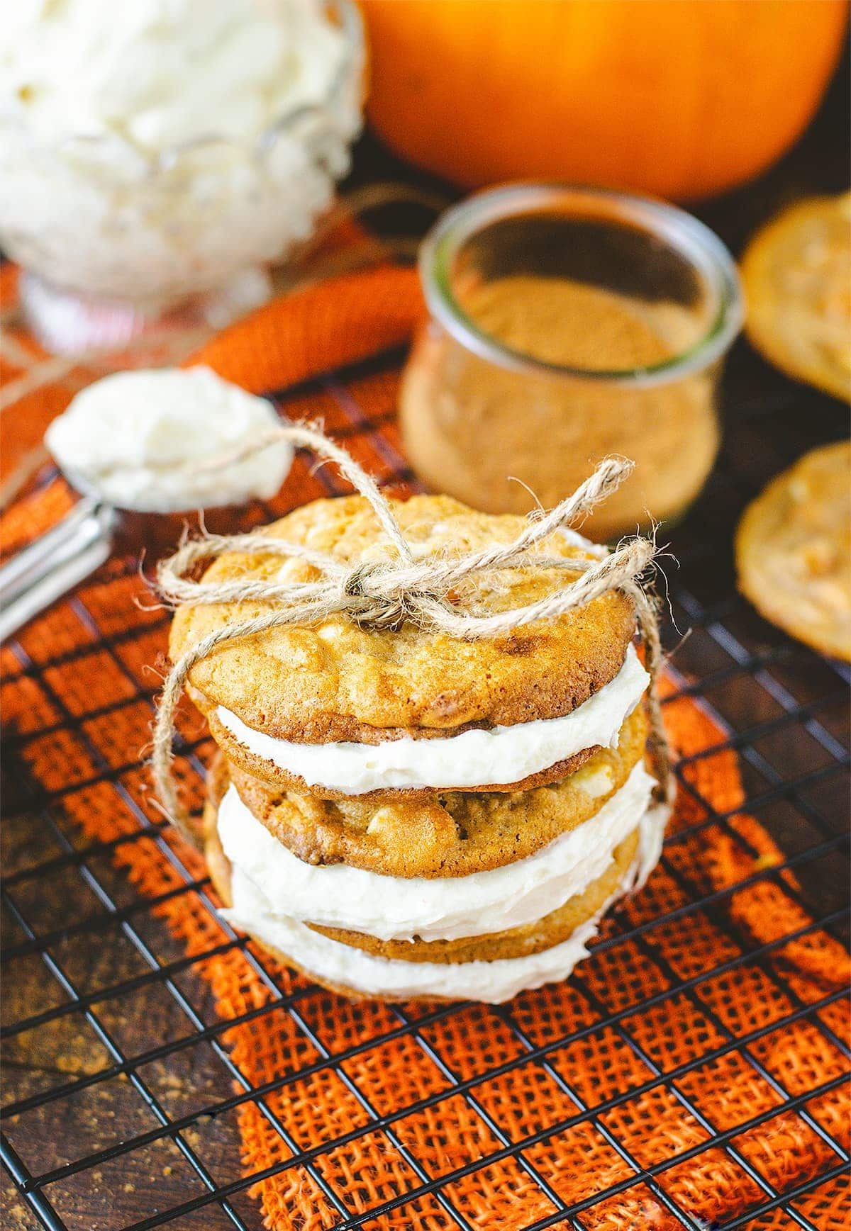 A stack of pumpkin spice sandwich cookies tied with twine ribbon.