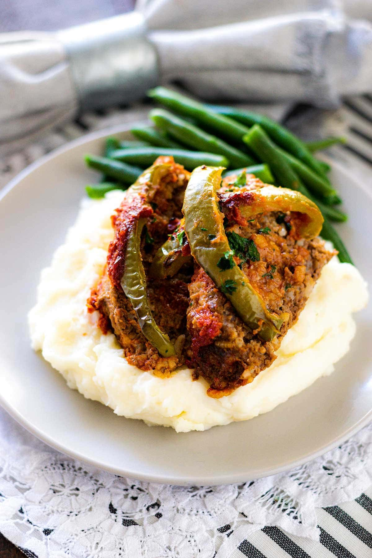 Meatloaf with all the flavors of stuffed peppers on top of mashed potatoes and a side of green beans.
