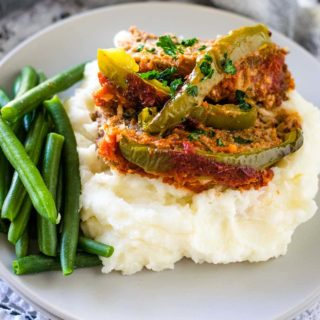 A plate stuffed pepper meatloaf over mashed potatoes served with fresh green beans.