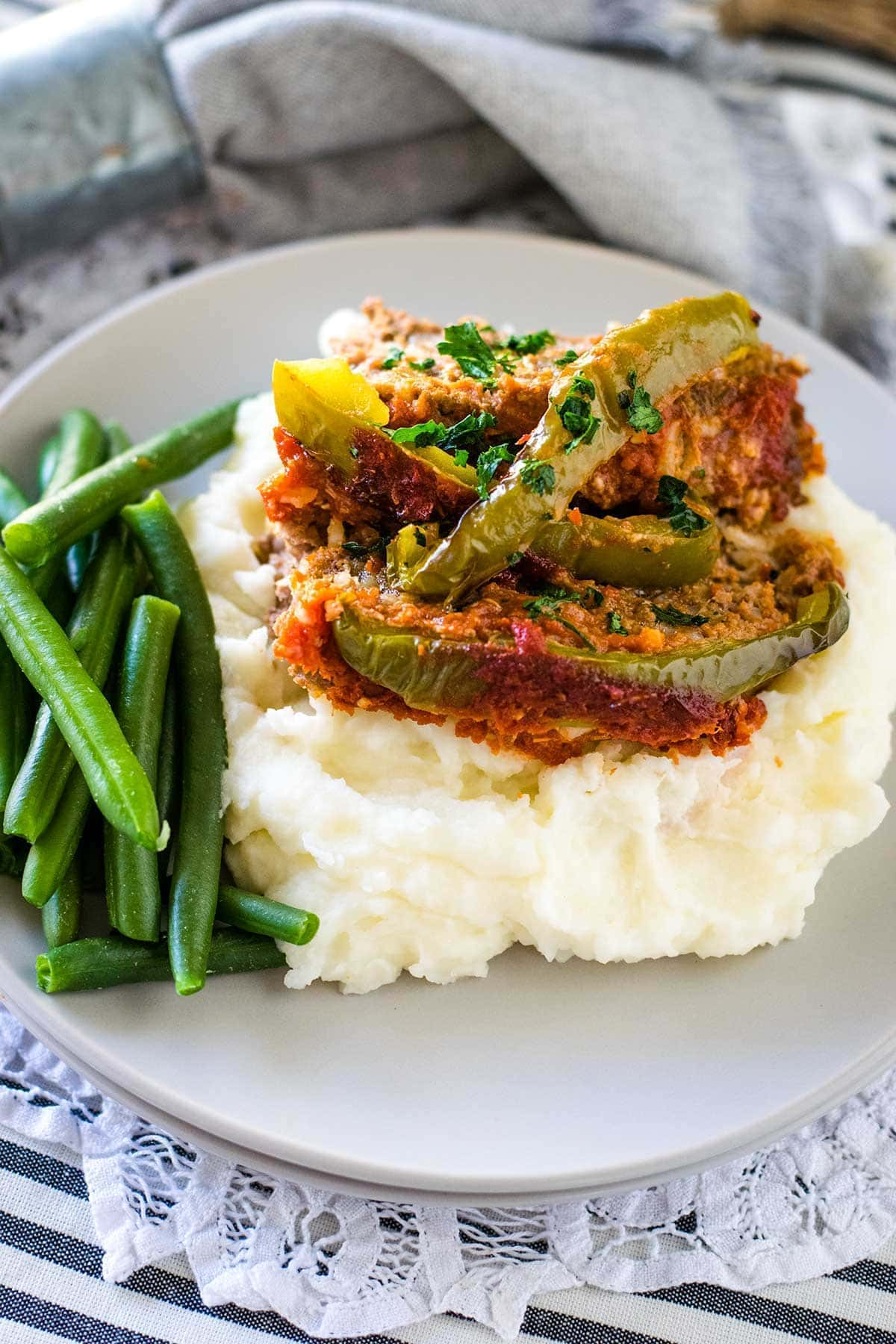 Slices of stuffed pepper meatloaf on a bed of creamy mashed potatoes with a side of fresh green beans.