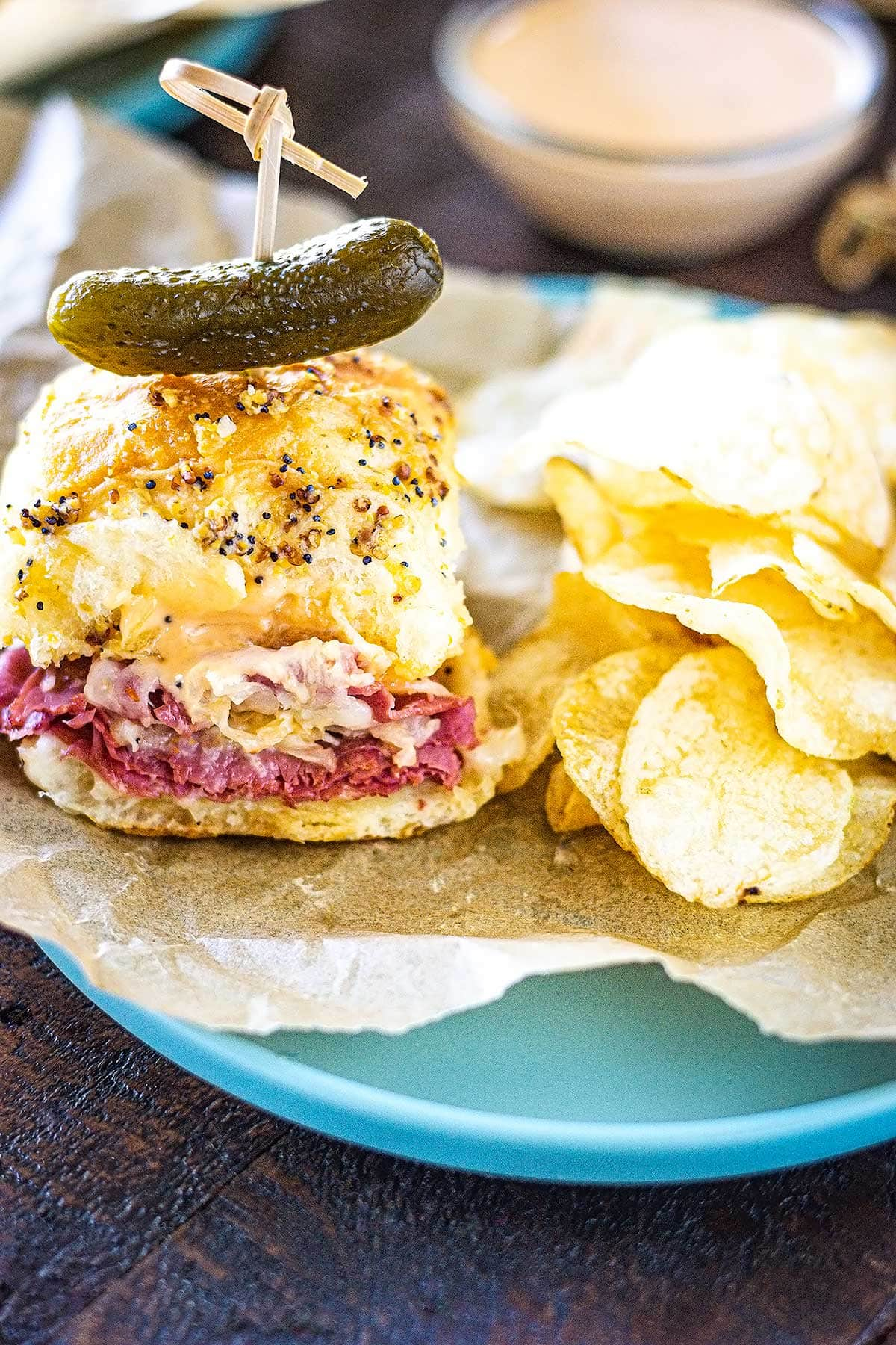A baked reuben sandwich slider topped with a pickle along with kettle chips on a plate lined with parchment paper.