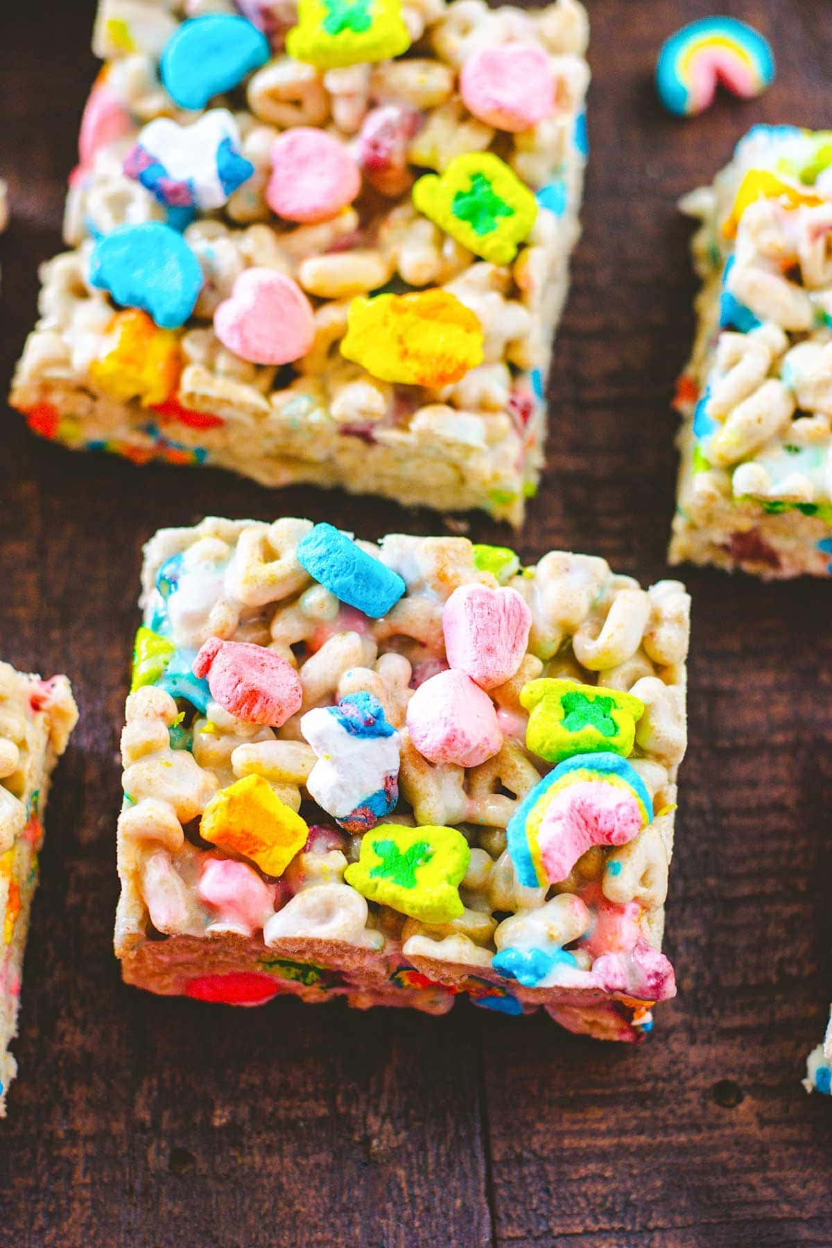 Sliced Lucky Charms treats on a wooden tray.
