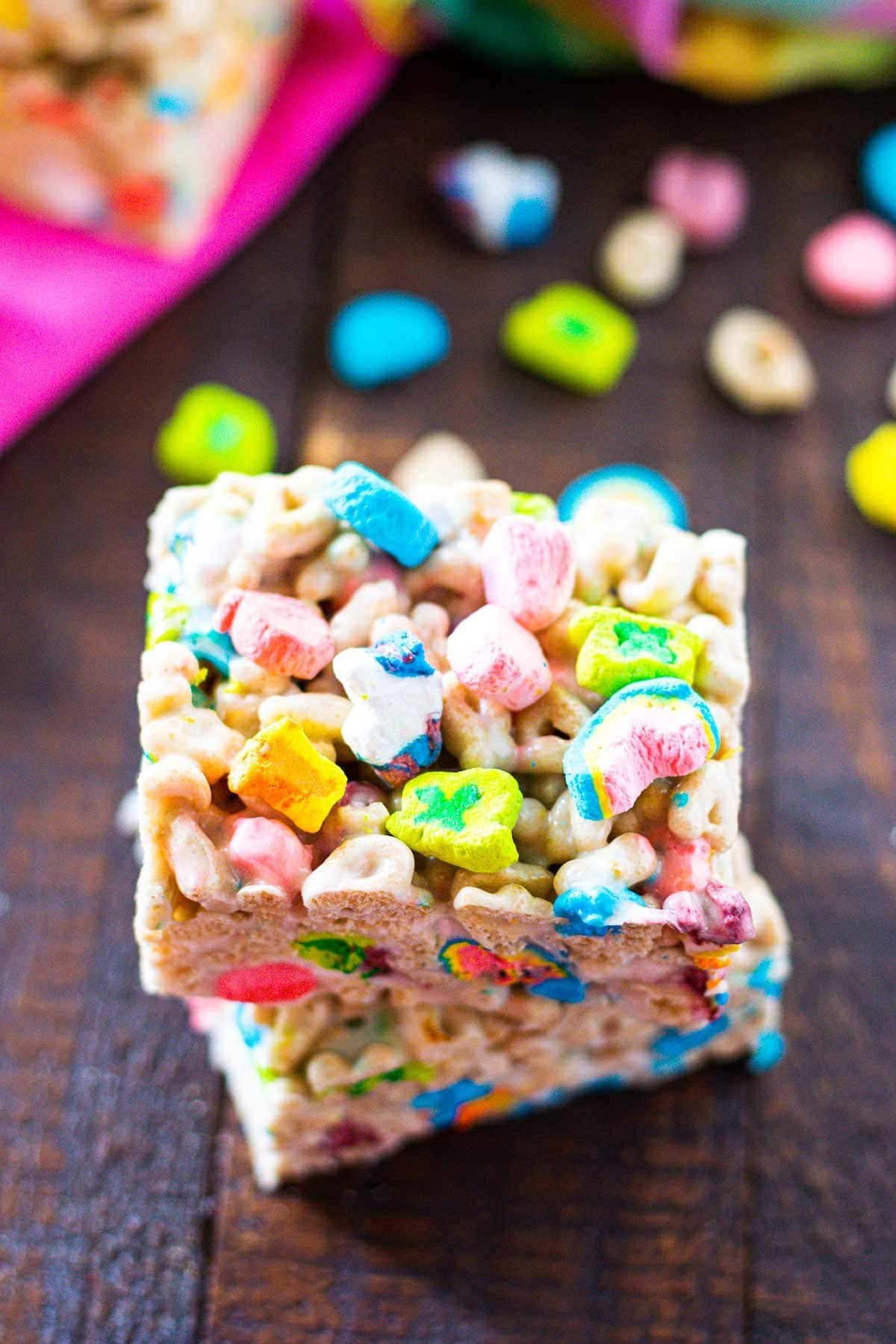 Lucky Charms Marshmallow Treats on a cutting board with Lucky Charms cereal scattered in the background.