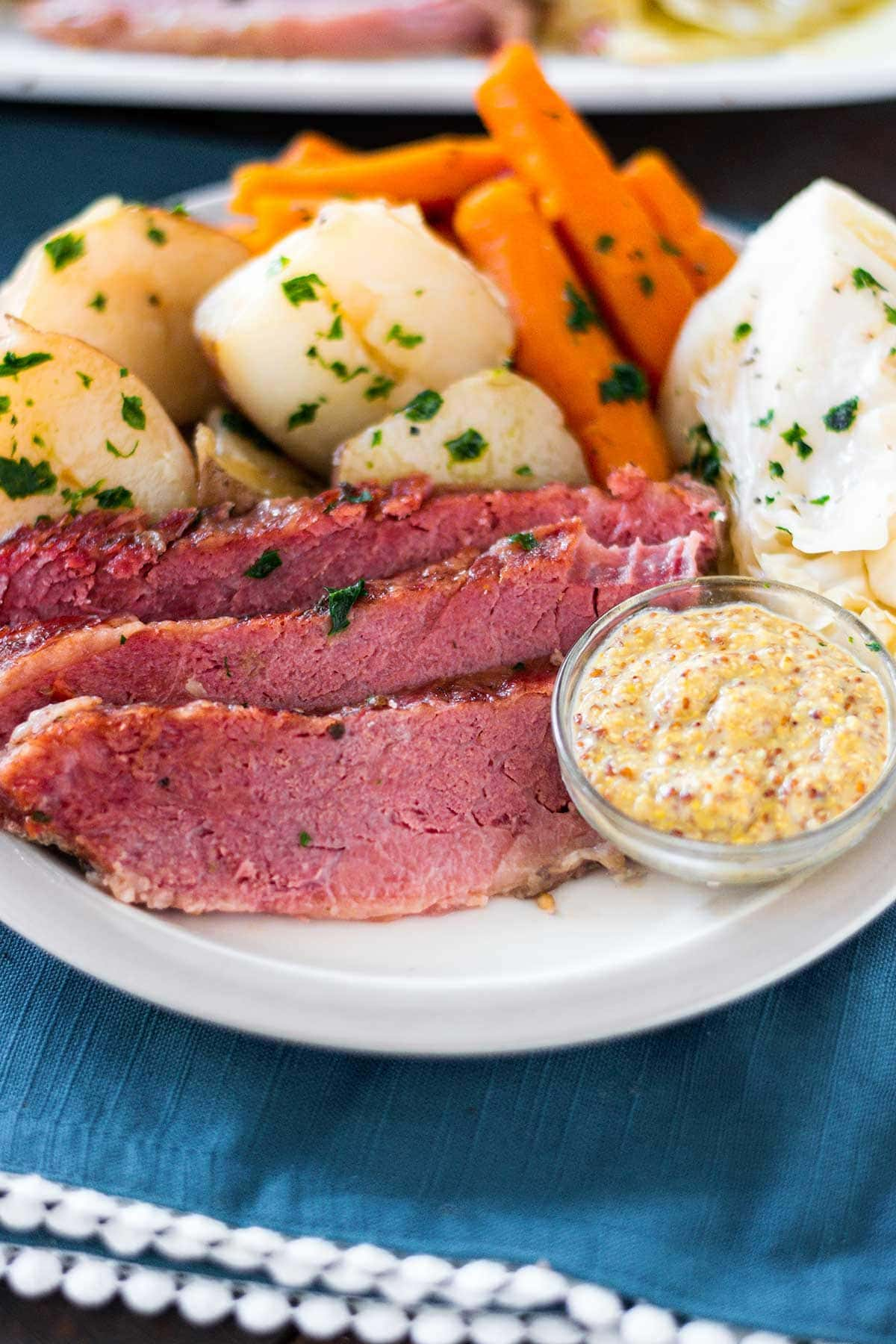 Corn beef and cabbage meal with potatoes and carrots on a white plate set on a blue placemat.