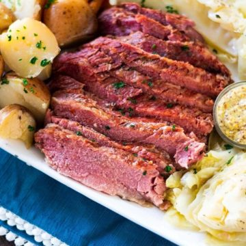 A plate of corned beef with potatoes, carrots, and cabbage.