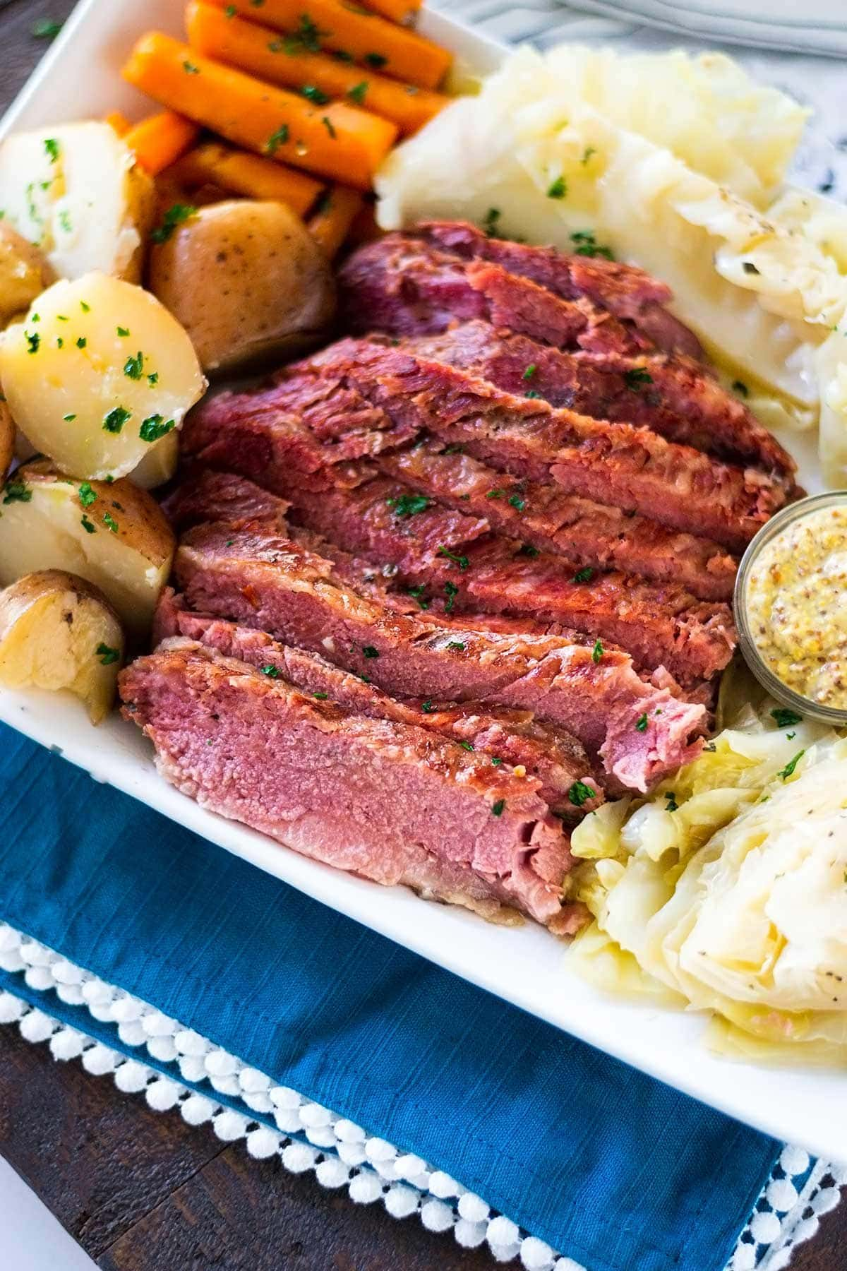 Sliced Slow cooker corned beef and cabbage on a white serving platter with red potatoes, carrots and spicy whole grain mustard.