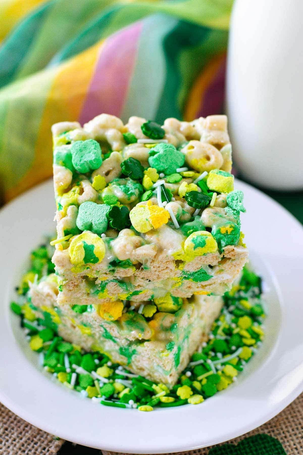 St. Patrick's Day themed Lucky Charms Cereal Treats in a white serving plate surrounded by St. Patrick's Day sprinkles.