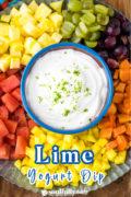 A sweet lime yogurt in a serving bowl on a fruit filled platter.