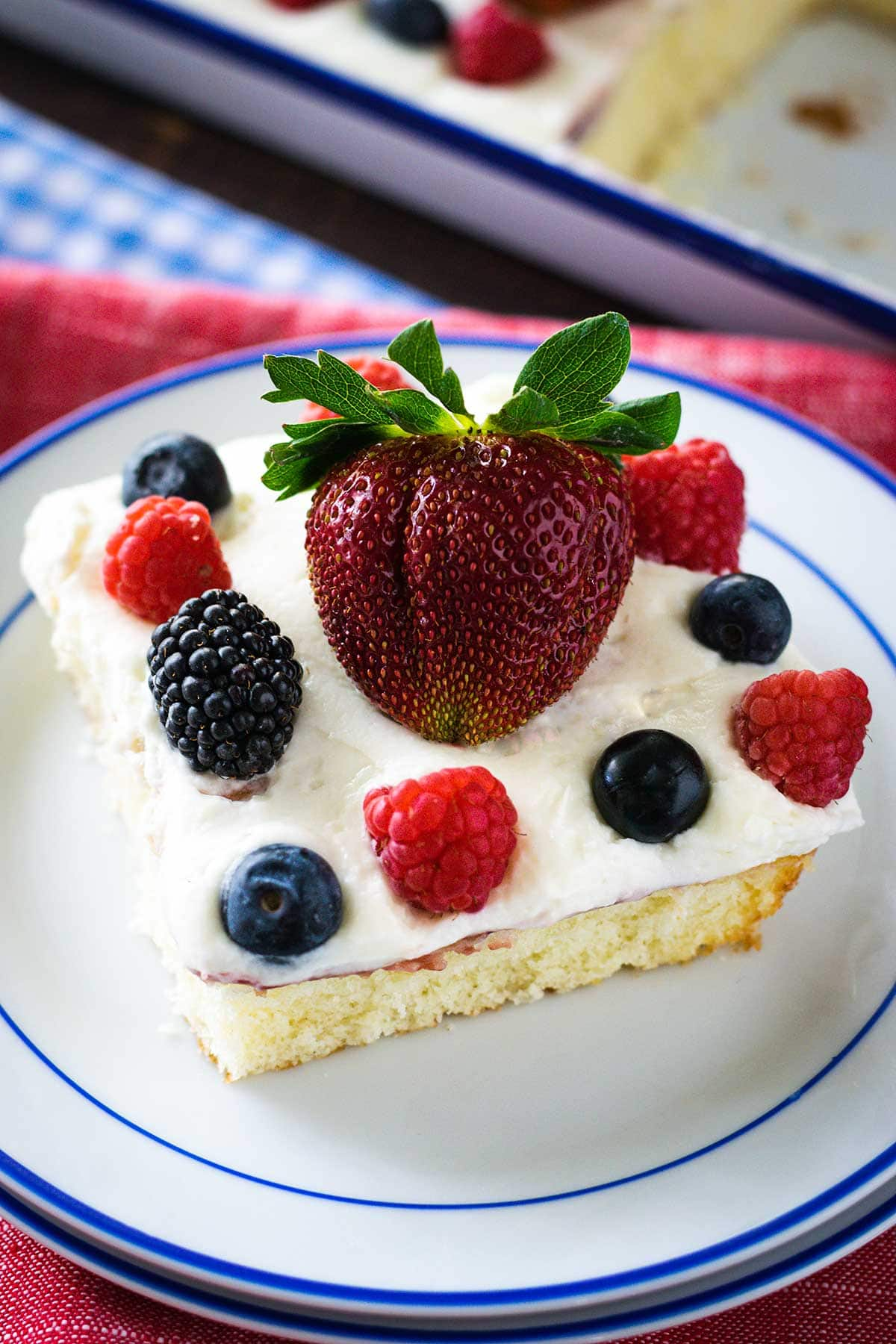Up close image of a slice of chantilly cake topped with fresh berries on a white plate with blue trim.