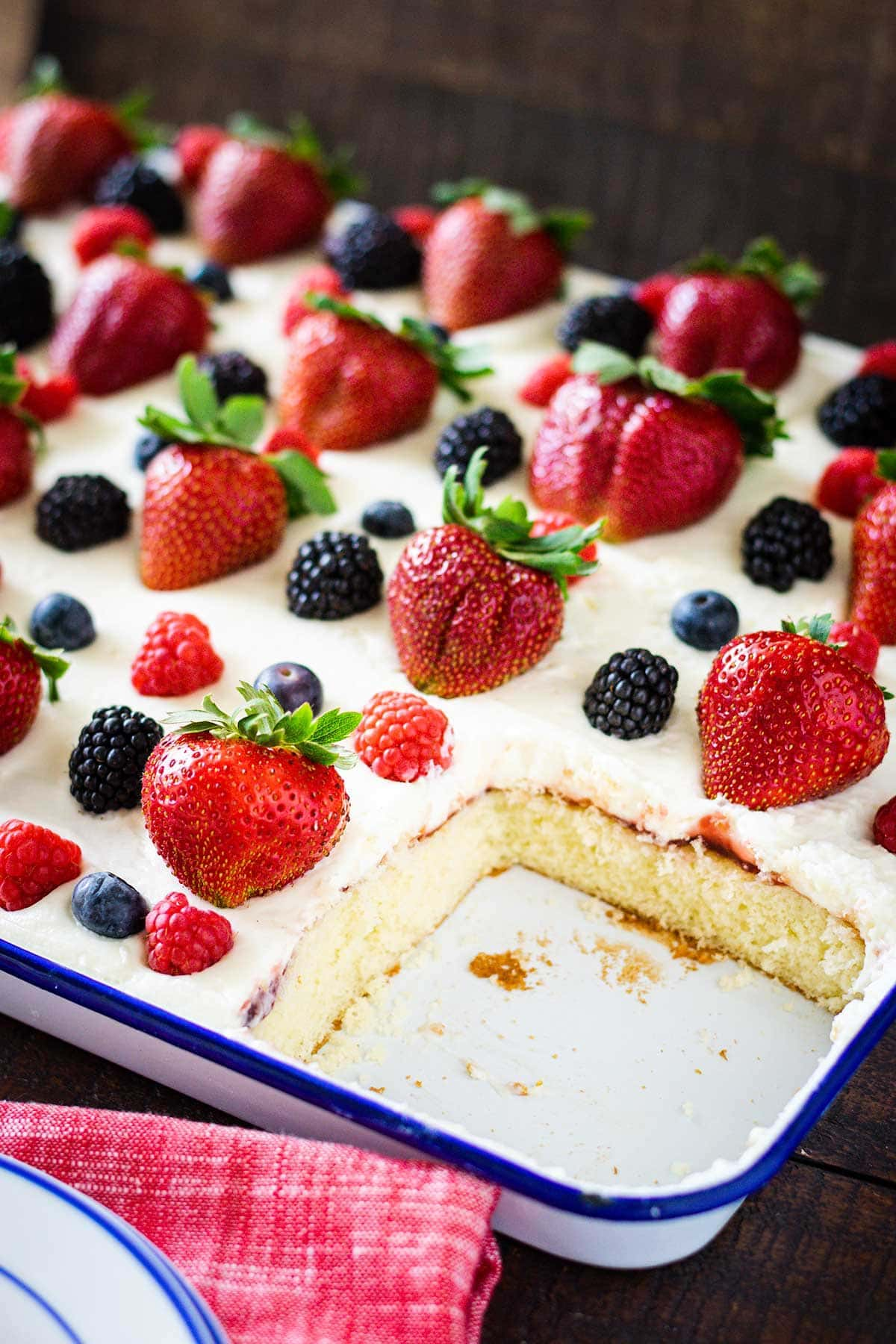 Chantilly sheet cake topped with fresh strawberries, raspberries, blueberries and blackberries. Set in a sheer pan with a slice remove showing the sponge cake.