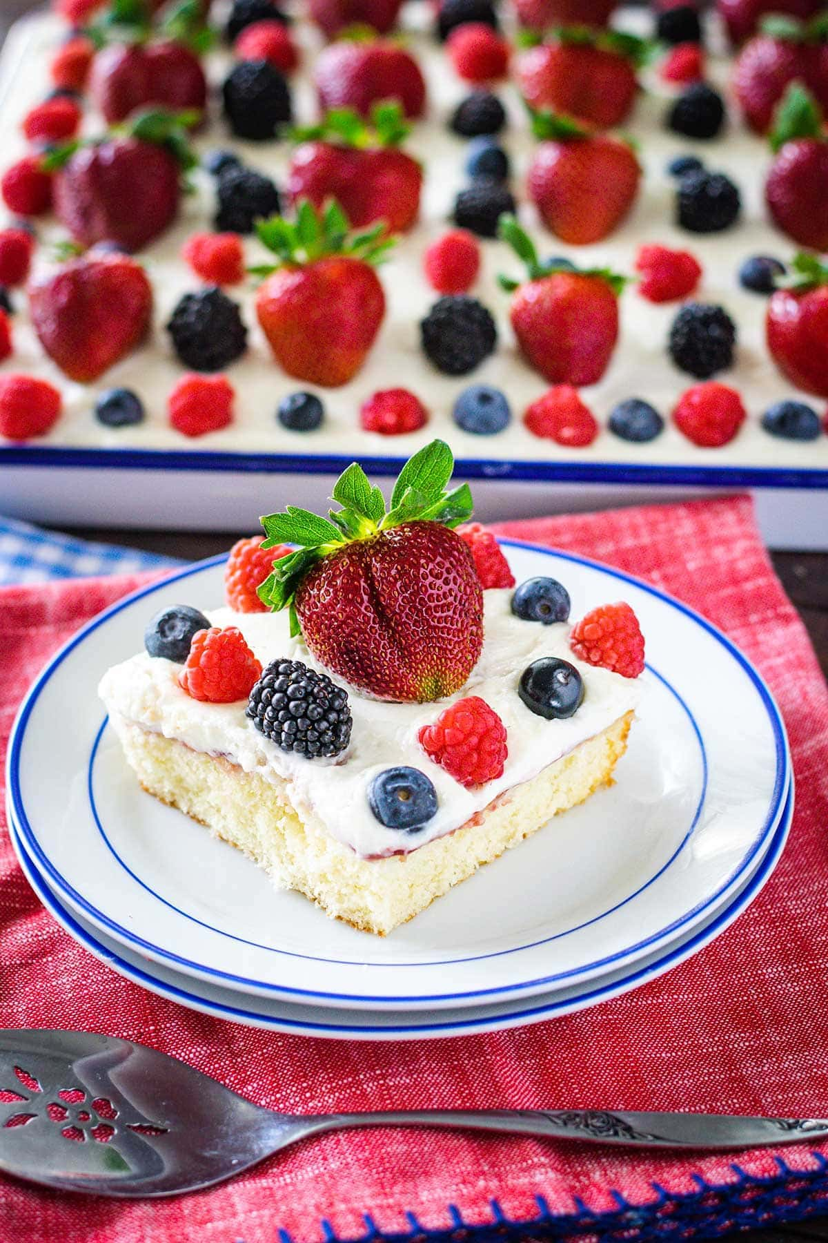 Slice of chantilly cake topped with fresh berries on a white plate with blue trim. Set on a red napkin with sheet cake in the background.