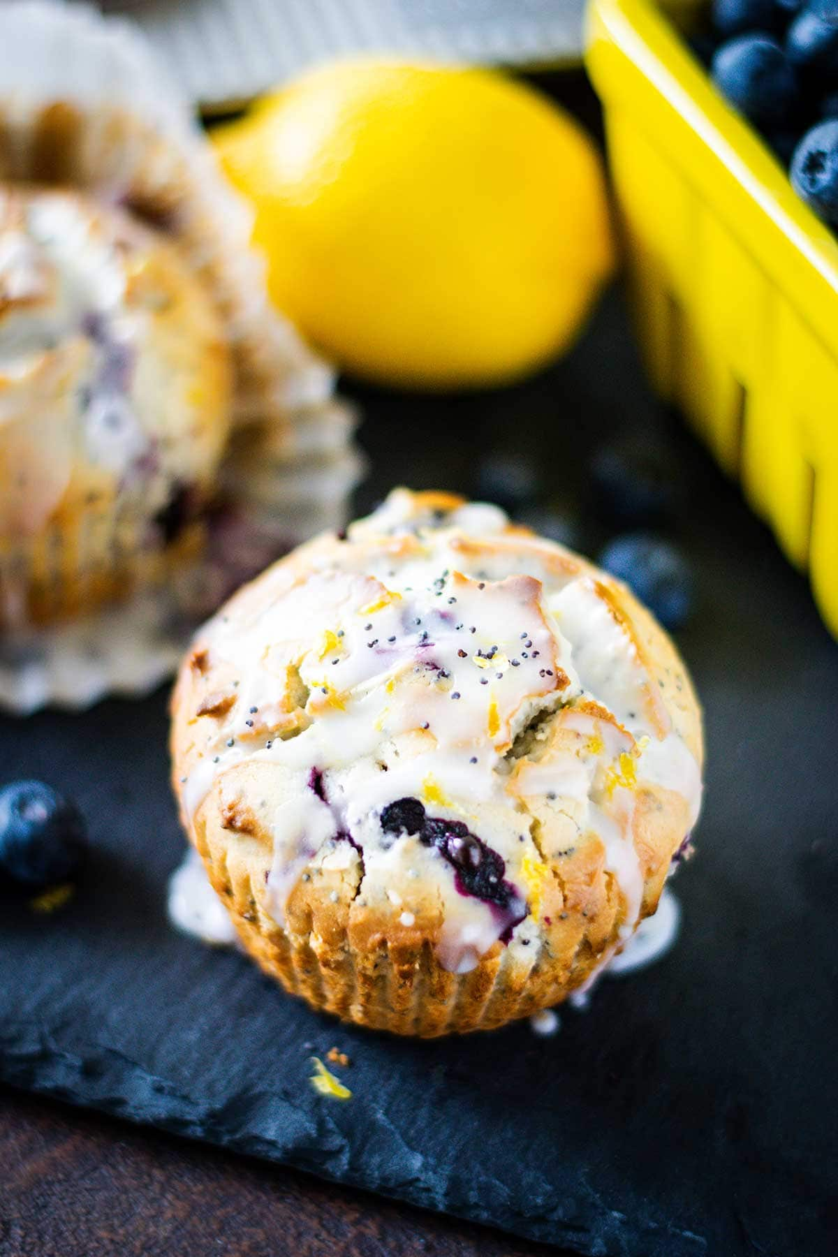 Blueberry lemon poppy seed muffin on a black tray with blueberries in the background.