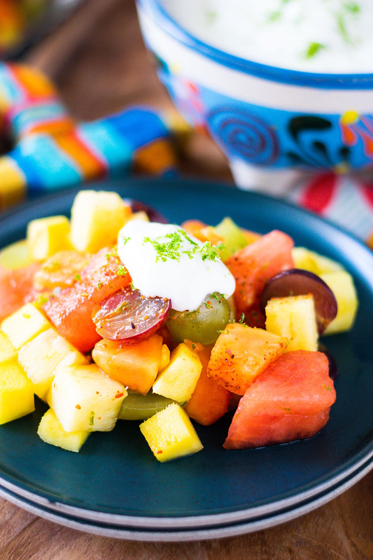Plated Mexican fruit salad with lime yogurt dolloped on top.