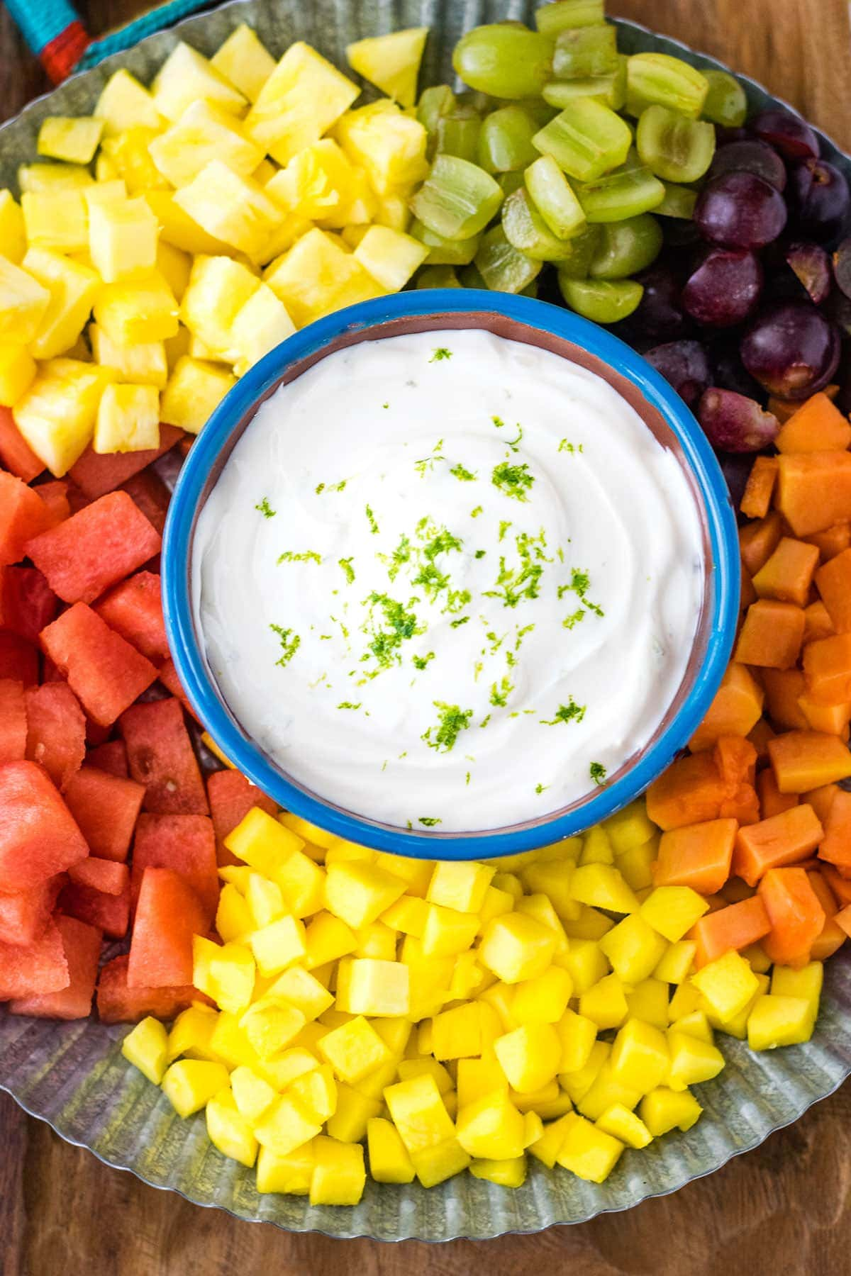 A sweet lime yogurt dip on a metal serving platter surrounded by tropical fruits.
