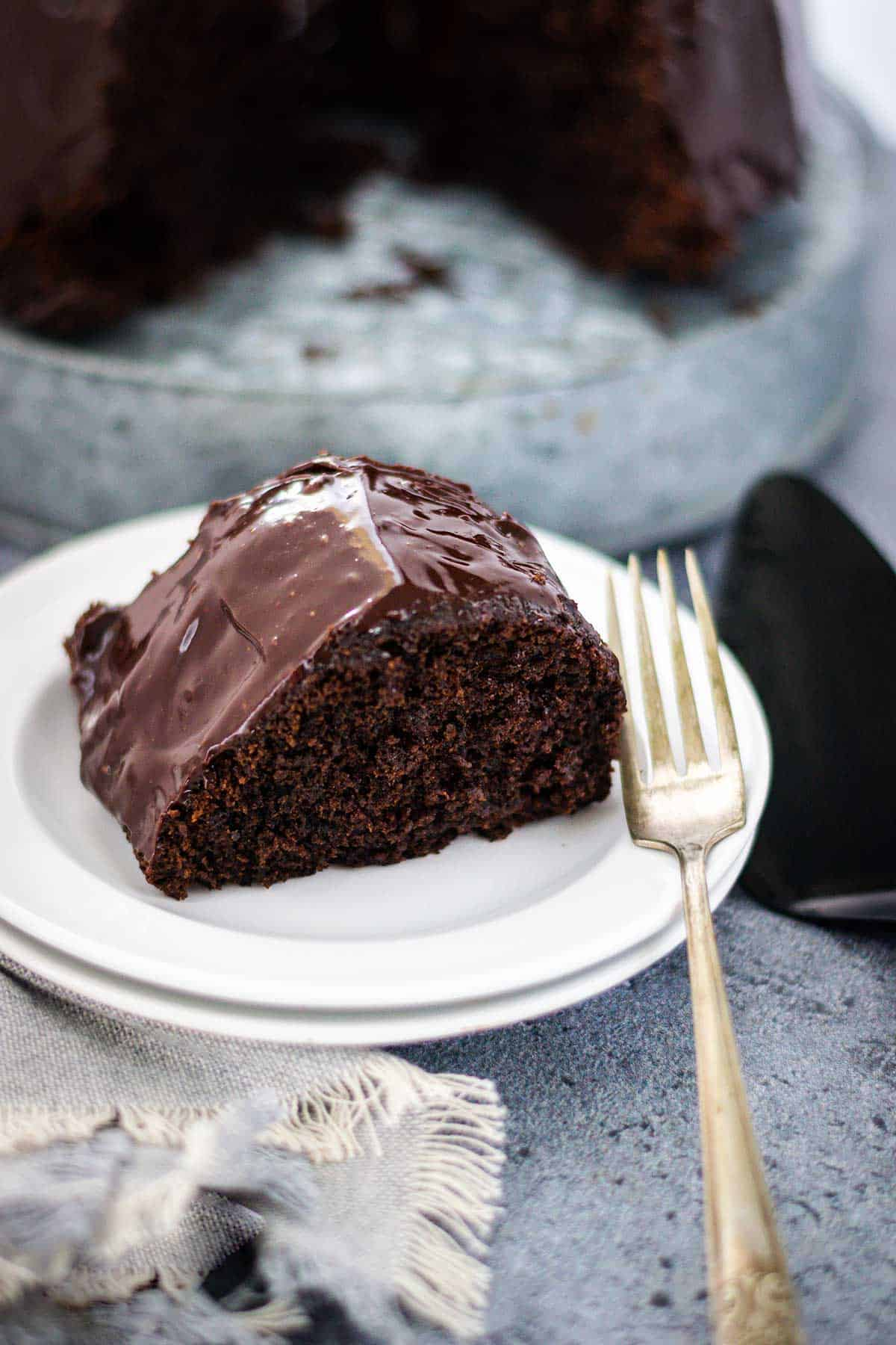 Chocolate brownie cake with a fork to the side. Place on a gray tablescape with a black cake server..