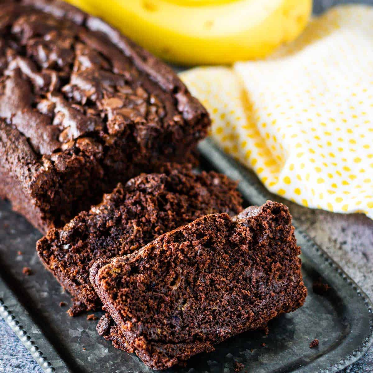 Slices of chocolate banana bread on a tray with yellow dotted napkin in background.