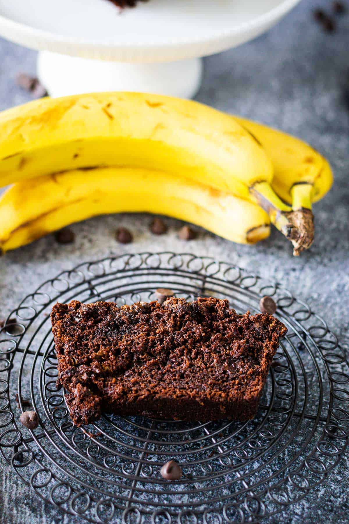 Slice of chocolate banana bread on a decorative round cooling wire with chocolate chips scattered and a banana in the background.
