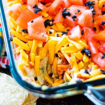 Mexican layer dip in a glass bowl with some of the dip removed.
