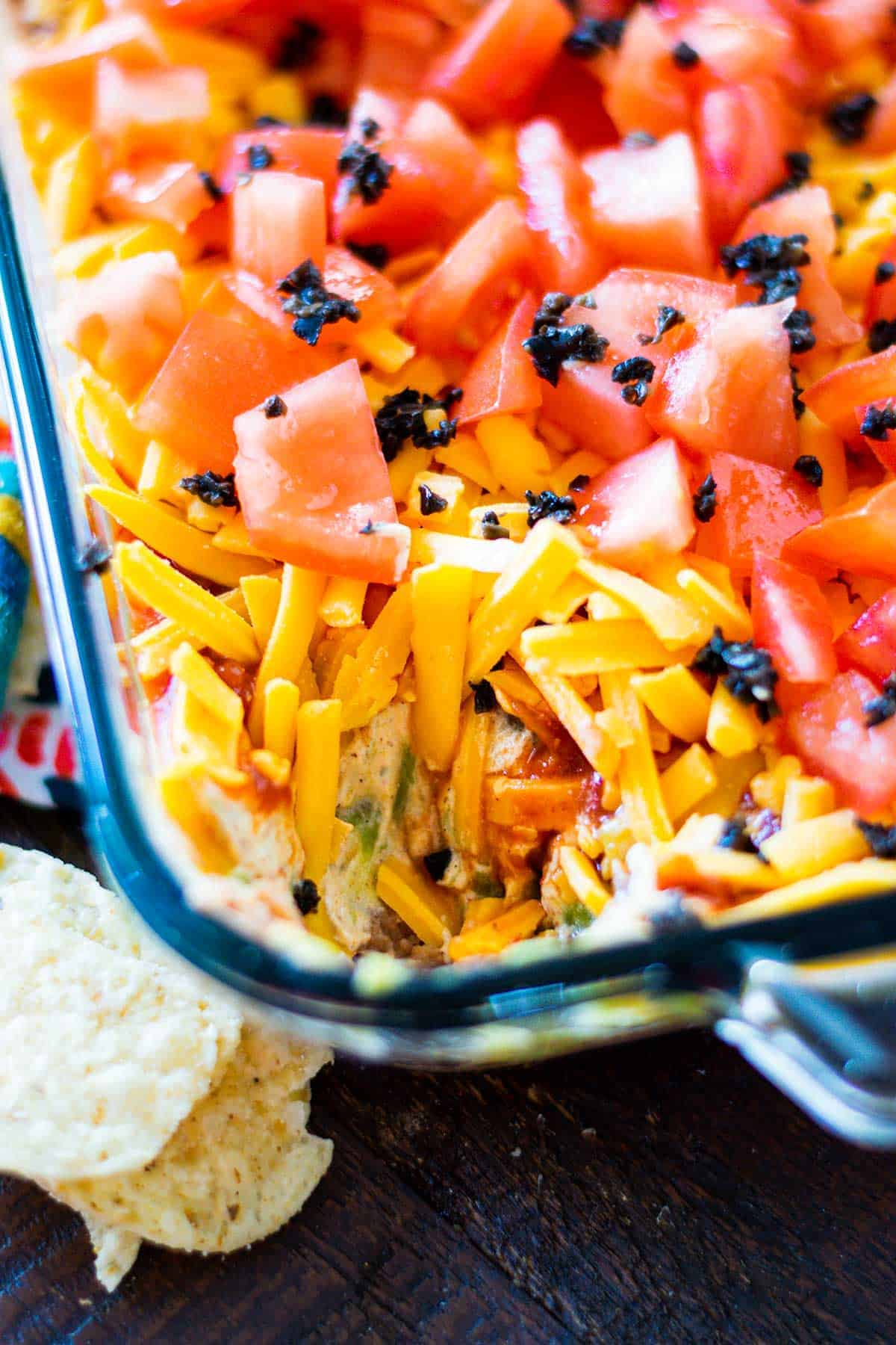 Image of a Mexican seven layer dip in a glass bowl with a scoop removed from the dish.