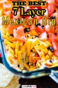 Pinterest image of a dish of Mexican Seven Layer Dip on a wooden table.
