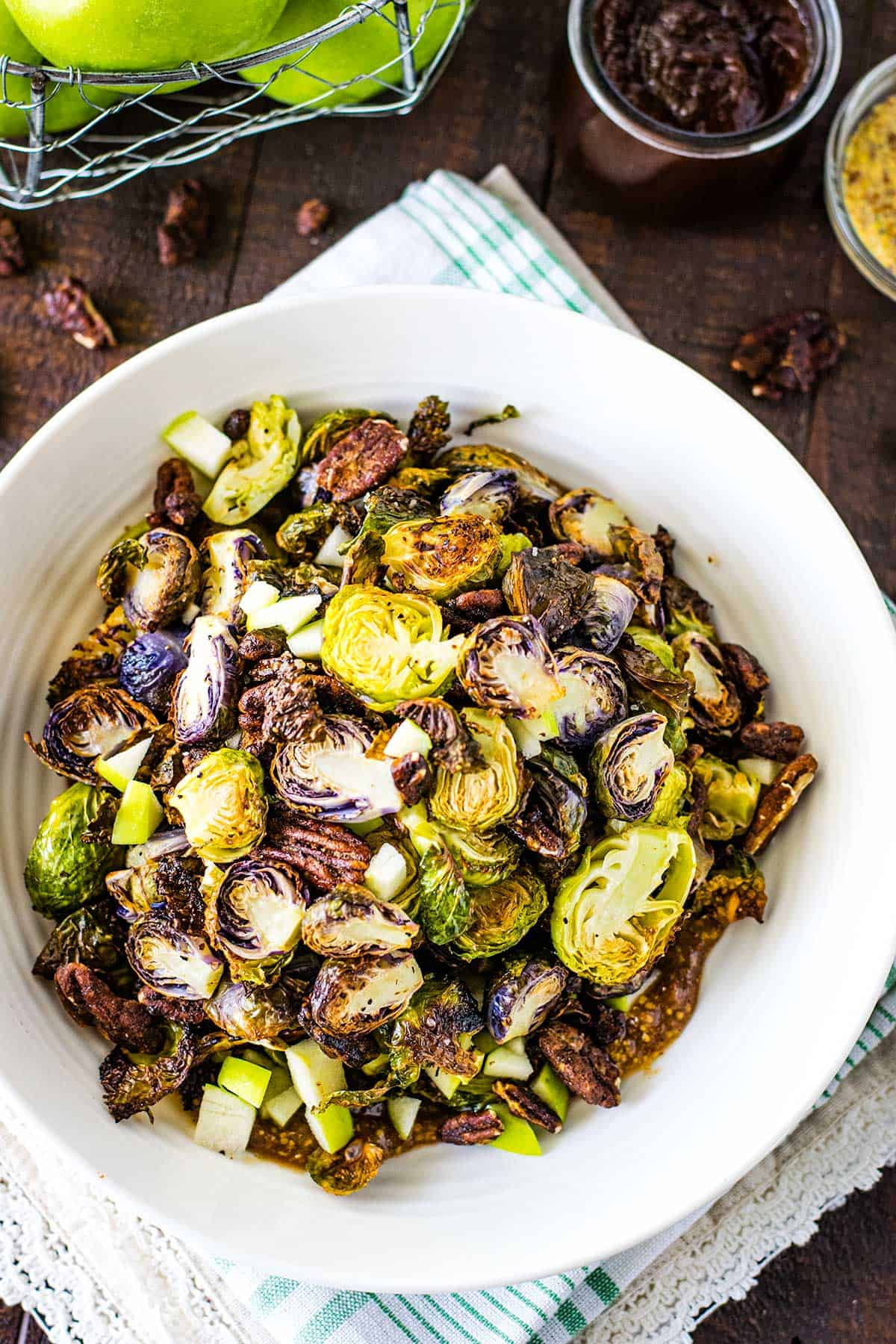 Overhead image of roasted brussels sprouts in a white bowl on a wooden table.