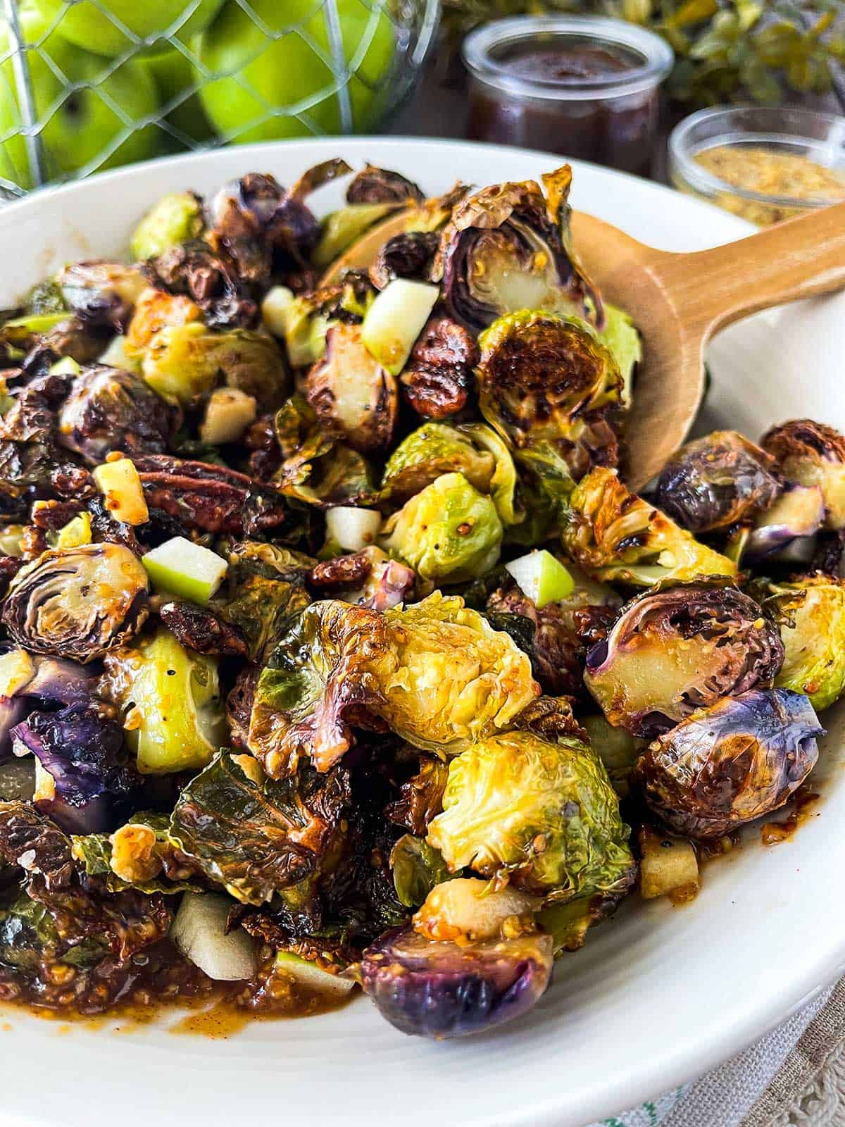 Upclose image of purple and green brussels sprouts with an apple butter dijon glaze topped with diced apples and pecans.