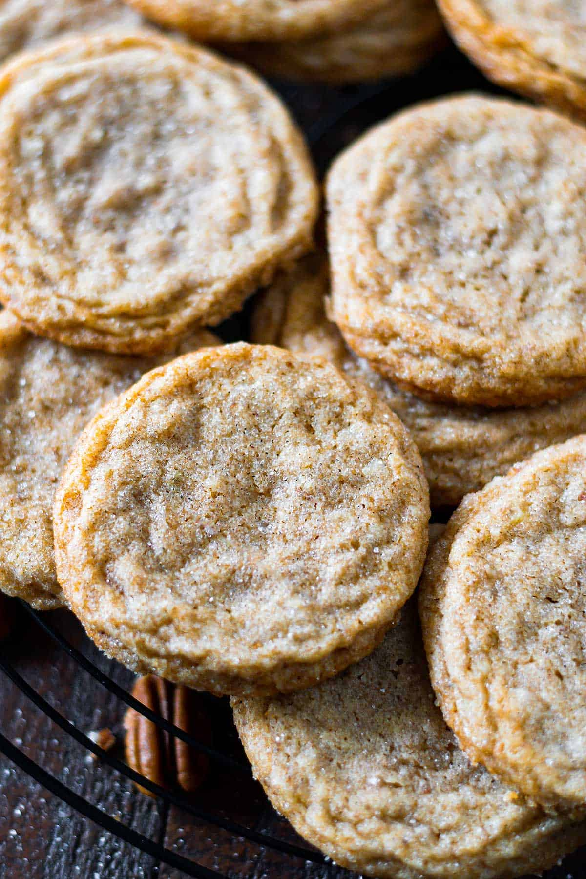 Up close image of a stack of pecan butter cookies on a wire baking rack.