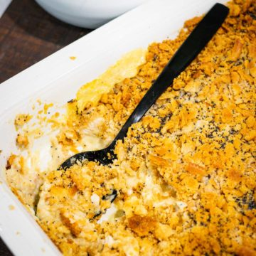 A white casserole dish with chicken poppy seed casserole scooped out of it.