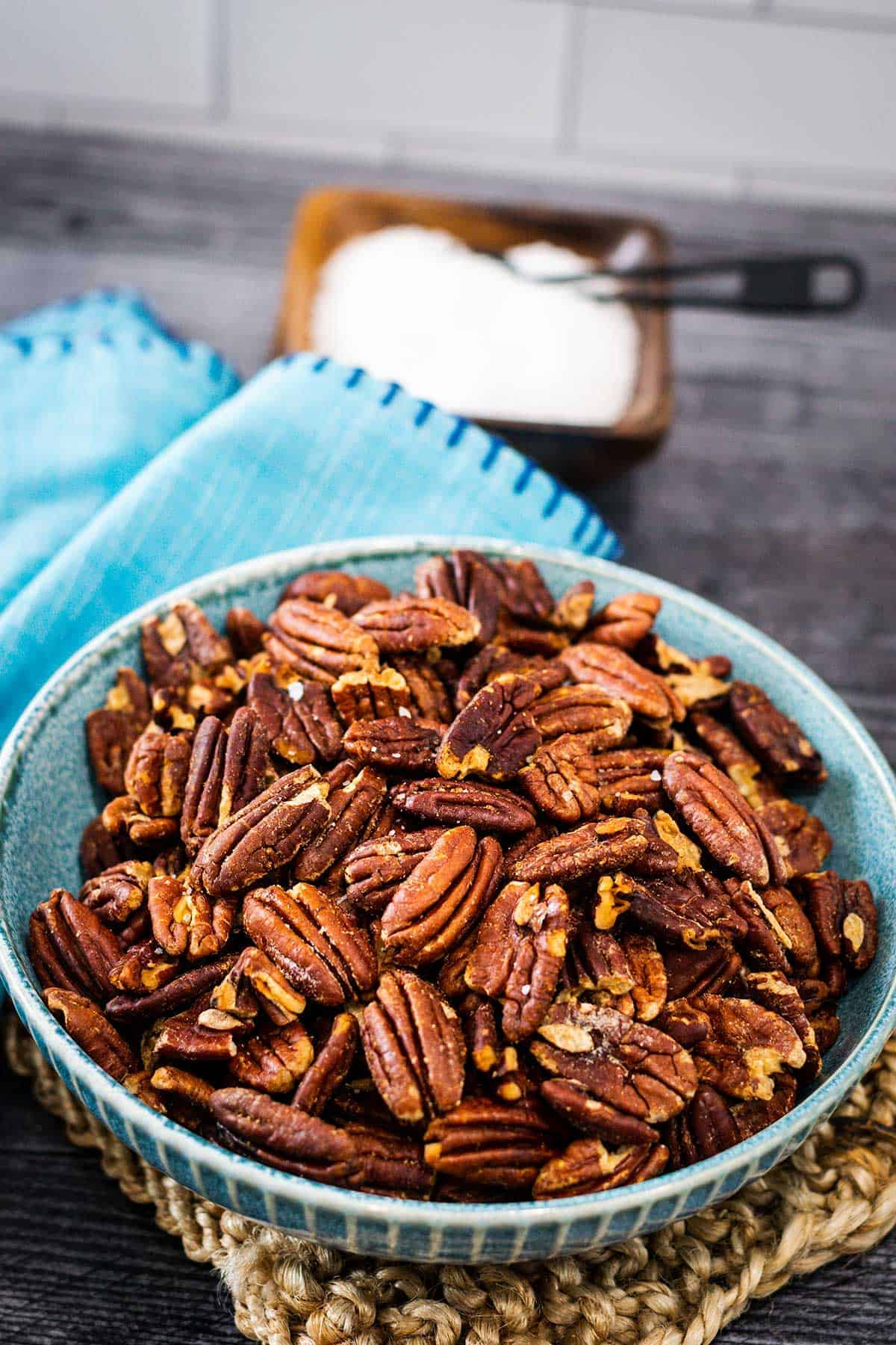 Bowl of toasted pecans sprinkled with sea salt in a blue bowl set on a wooden table.