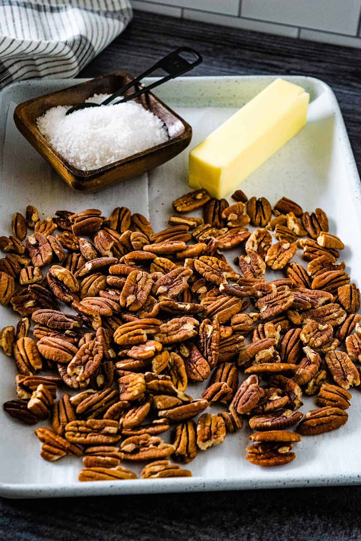 Toasted pecan ingredients pecans, butter, and salt on a white baking tray.