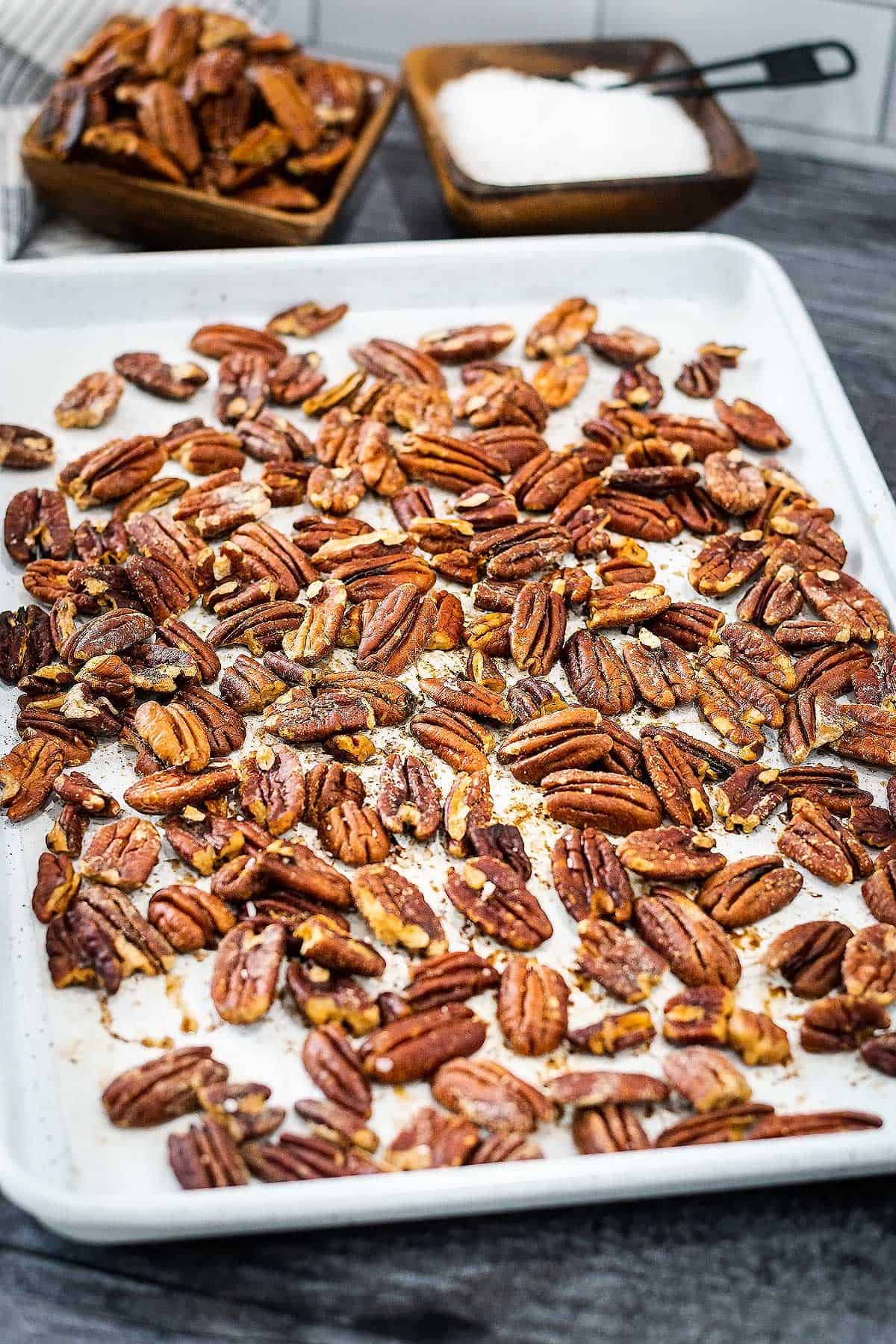 Roasted pecans fresh out of the oven on a baking tray.