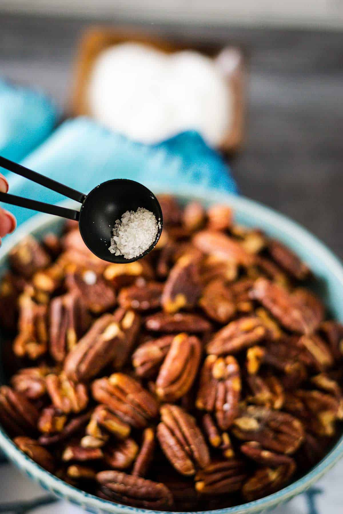 Toasted pecans in a blue bowl being topped with salt.