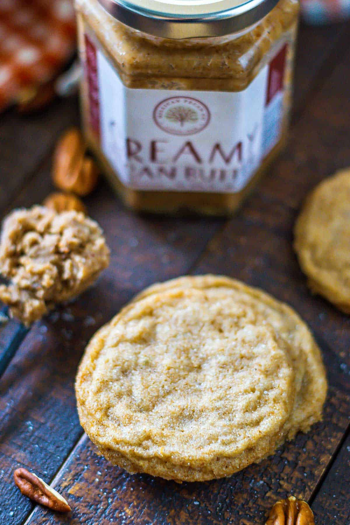 Pecan butter cookie on a wooden tablescape with jar of Millican Pecan Butter in the background.